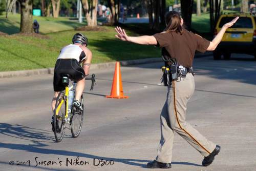 A police officer directs traffic as a cyclist goes by.