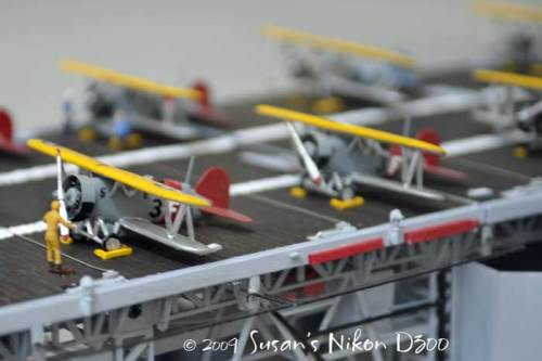 Miniature planes line the deck of a model of the USS Essex.