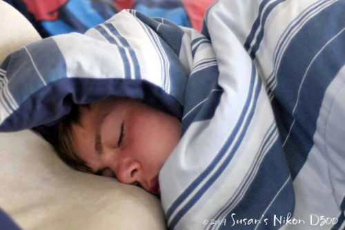 The #2 son sleeps soundly in bed.