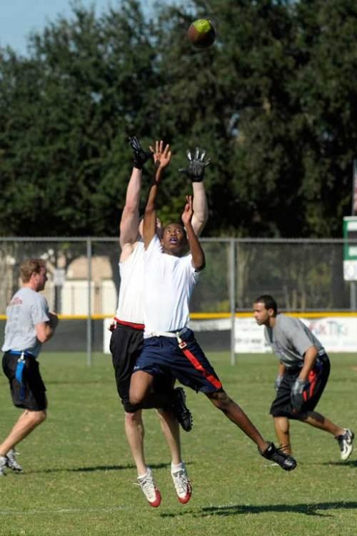 Sam and Omar both jump high for the football.
