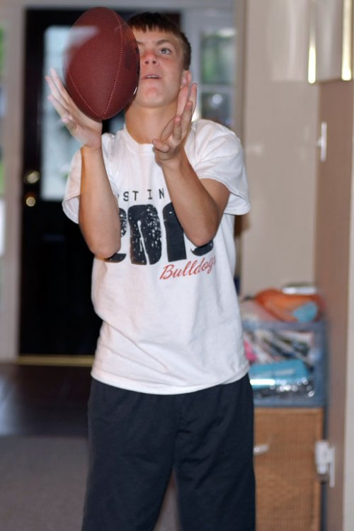The #2 son catches a football he tossed to himself.