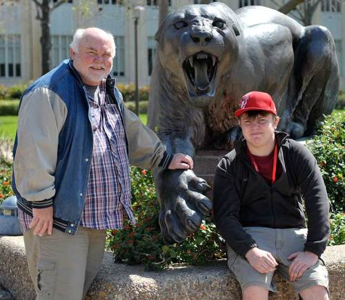 Dad and son are glad the fierce cougar is just a statue!