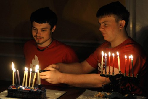 Younger helps older keep his candles lit