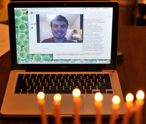 My older son smiles via Skype as the sixth-night candles glow.