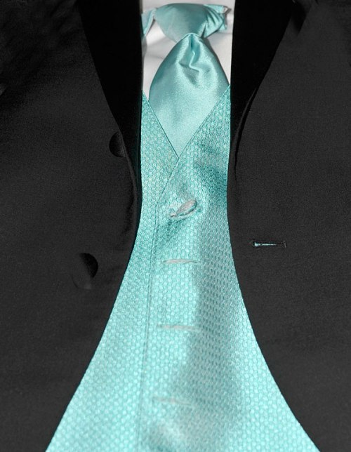 The turquoise vest and necktie matches his date's dress . . . we hope.