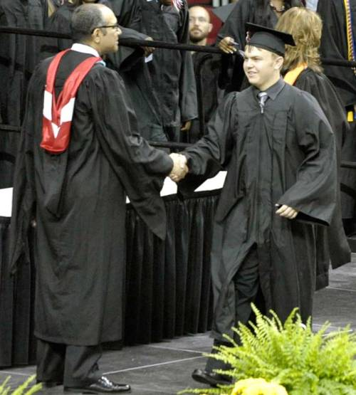 The kid shakes hands with the school district's superintendent at his high school graduation last Saturday.