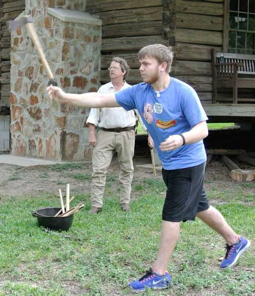 The kid tries his hand at tomahawk tossing.