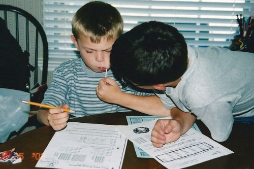 Older brother helps his younger sibling with his homework 10 years ago.