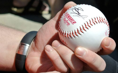 C.J. holds the ball with his first autograph.
