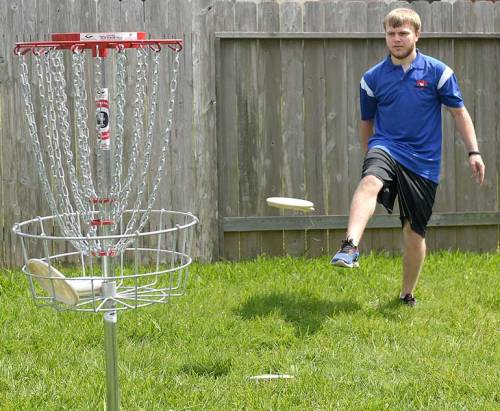 C.J. starts a disc towards the basket in an unconventional manner.