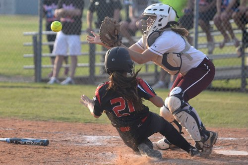 Callie bears down on the plate as the catcher awaits the throw.