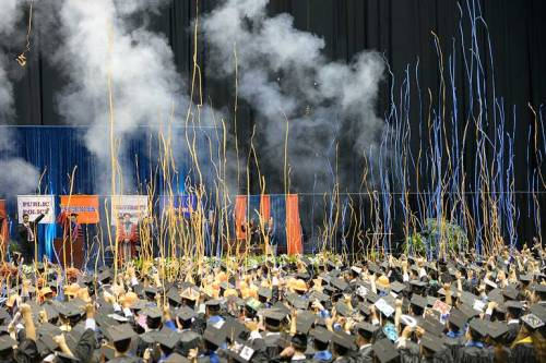 The smoke from indoor fireworks and streamers rain down on the graduates.